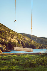 Swing hanging on tree on the island of Vis, with sea in the background