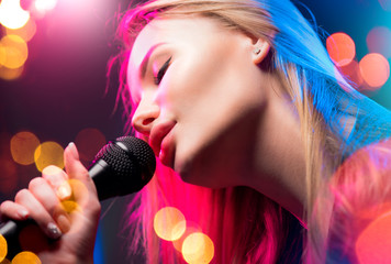 Beautiful Singing Girl. Beauty Glamour fashion Woman with Microphone over Blinking bokeh night background. Glamour Model Singer. Karaoke song, party. Rock star singer on music concert
