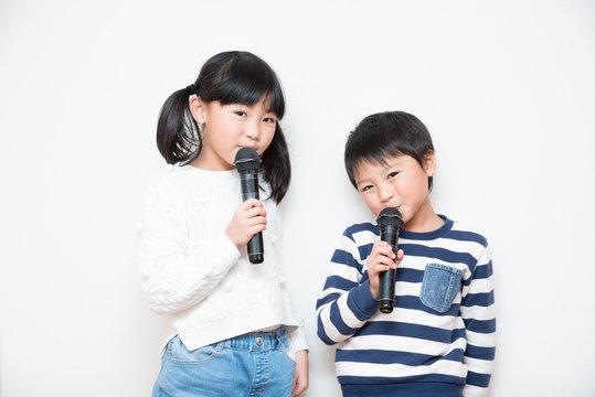マイクで歌う男の子と女の子