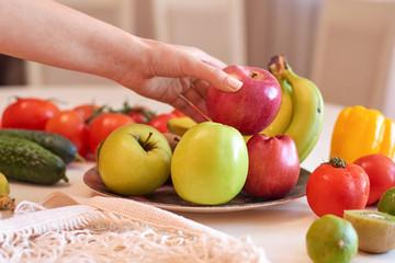 Keuken foto achterwand Koken Woman hands holding red apple above plate