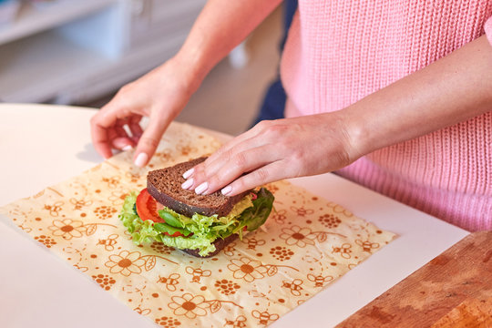 Woman hands wrapping a healthy sandwich in beeswax food wrap