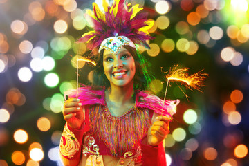 Foto op Canvas Carnaval Beautiful young woman in carnival mask and stylish masquerade costume with feathers and sparklers in colorful bokeh on black background. Christmas, New Year, celebration. Festive time, dance, party.
