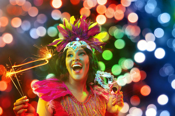 Beautiful young woman in carnival mask and stylish masquerade costume with feathers and sparklers in colorful bokeh on black background. Christmas, New Year, celebration. Festive time, dance, party. Wall mural