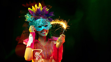 Beautiful young woman in carnival mask, stylish masquerade costume with feathers and sparklers inviting. Flyer for ad on black background. Christmas, New Year, celebration. Festive time, dance, party.