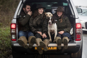 Attendees take a lift in a car after watching members of the Old Surrey Burstow and West Kent Hunt ride during the annual Boxing Day hunt in Chiddingstone, Britain
