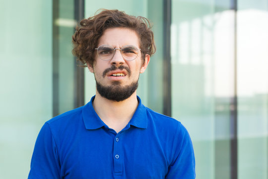 Clueless puzzled guy looking at camera with questioning face, having no idea. Handsome bearded young man in blue casual t-shirt standing at outdoor glass wall. Asking concept