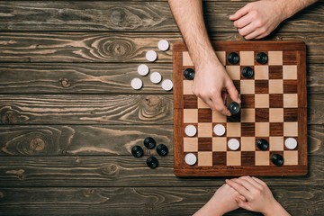 Top view of couple playing checkers on wooden background