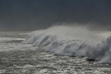 Dark long spraying sea wave