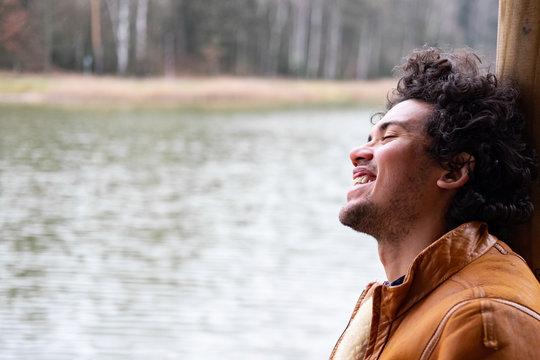Latin American man looking happy at a lake