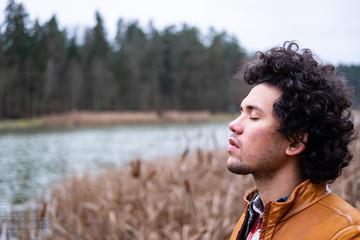 Latin American man looking relaxed at a lake