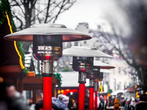 row of gas patio heaters with propane heat lamp on the street in winter day
