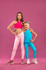 Two children girls rest after fitness exercises on a pink background. Kids lifestyle concept.
