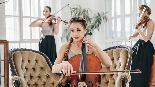 Three Other Women Are Playing Violins On The Background.