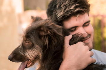 Stock photo of a young man hugging a brown dog, friendly concept animal, best friends.