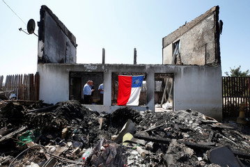 Chilean flag hangs off the remains of a house after it was destroyed by fire in Valparaiso