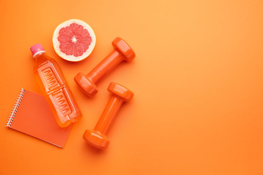 Dumbbells with notebook, grapefruit and bottle of water on color background