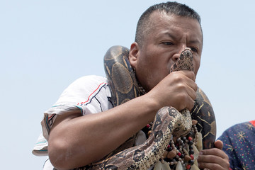 A Peruvian shaman kisses a boa constrictor snake during a ritual of predictions for the new year at Pescadores beach in Chorrillos, Lima