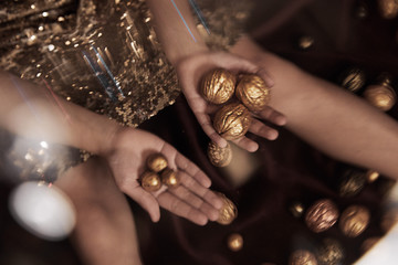 Golden painted nuts in childs hands on the golden and black background