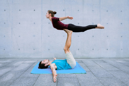 Couple practicing acro yoga outdoors. Acroyoga concept. Front Bird pose