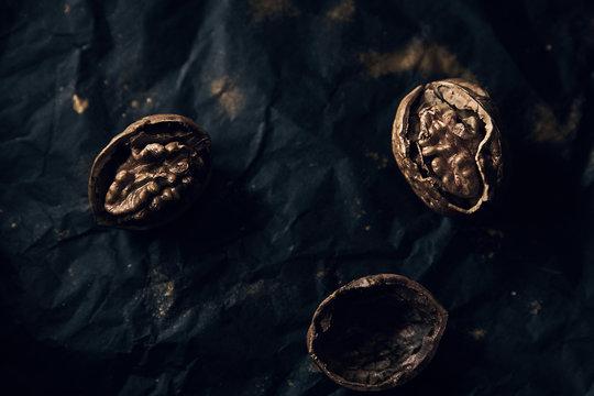Three golden walnuts and nutshells on black paper