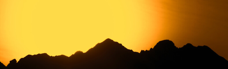 Poster de jardin Melon Big mountains on a background of orange sunset. Beautiful panorama of the mountains