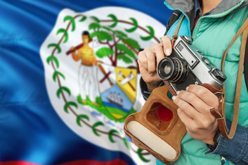 Belize photographer concept. Close-up adult woman holding retro camera on national flag background. Adventure and traveler theme.