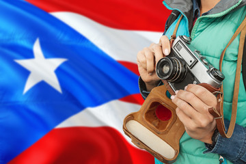Puerto Rico photographer concept. Close-up adult woman holding retro camera on national flag background. Adventure and traveler theme.