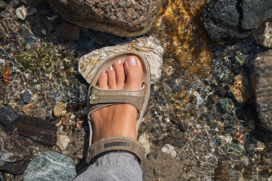Women's tanned legs in open sandals on a summer hike on a mountain river. Travel concept, the concept of Hiking.