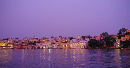 Wall Mural - Udaipur Lal ghat, houses and City Palace on bank of lake Pichola with water ripples - Rajput architecture of Mewar dynasty of Rajasthan. Sunset at Udaipur, India. Horizontal panning
