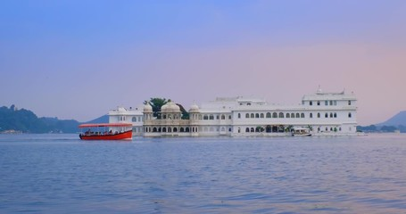 Wall Mural - Udaipur Lake Palace Jag Niwas on island on lake Pichola with tourist boats - Rajput architecture of Mewar dynasty rulers of Rajasthan. Sunset at Udaipur, India