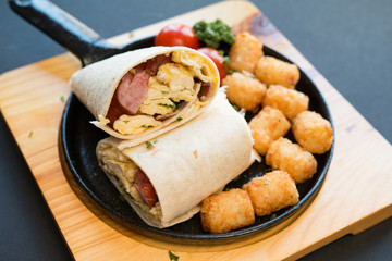 Breakfast burrito with sausage and scrambled egg and hash brown on a wooden plate