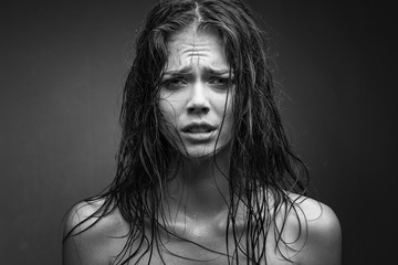 Expressive black white portrait of a young attractive girl with wet dark hair