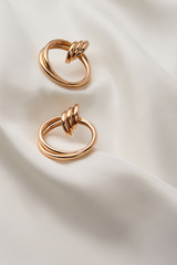Subject shot of a pair of golden earrings isolated on the white textile surface. Each earring is made as a set of three glossy rings and a large double hoop