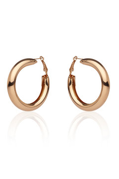 Subject shot of a pair of golden earrings isolated on the white background with reflexion. Each earring is made as a glossy puffed hoop.