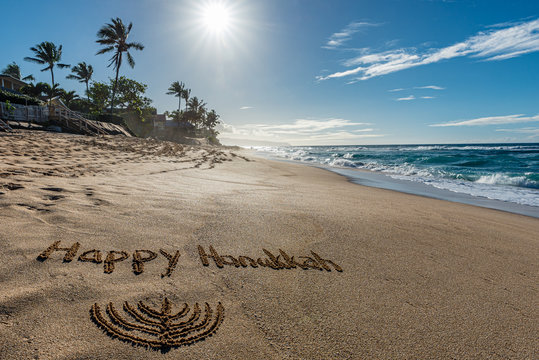 Happy Hanukkah written in the sand with a Hanukkiah with a tropical beach and ocean in the background