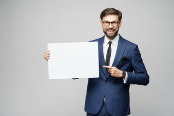 Fototapeta Young businessman holding blank signs over grey background obraz