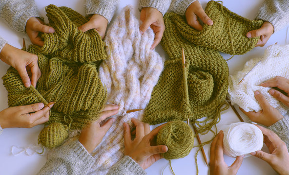 group of woman hand with knitting needles, knit wool white and mossy green scarf for winter handmade gift