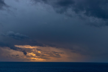 A dramatic set of clouds, at sunset, drifting over the tropical waters of the Caribbean Sea are lit by the last moments of daylight.