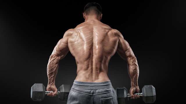 Muscular male model bodybuilder doing exercises with dumbbells, turned back. Strong muscular back of male bodybuilder. Isolated over black background.