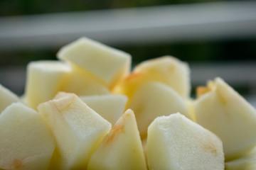 Primer plano de cubos de manzana pelados, en un plato y algo oxidados (marrones) después de cortarlos.