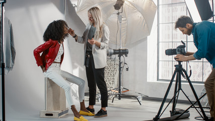 Backstage of the Photo Shoot: Make-up Artist Applies lipstick Makeup on Beautiful Black Model with Lush Curly Hair. Photographer Preparing to Take Pictures. Fashion Magazine Studio Photoshoot