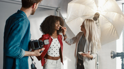Backstage of the Photo Shoot: Make-up Artist Applies lipstick Makeup on Beautiful Black Girl. Professional Model Getting Ready for Photoshoot for a Fashion Magazine in a Studio.
