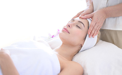 A beautiful woman slept with eyes and massage the face and head at the spa.