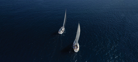 Aerial drone ultra wide photo of beautiful sailboat cruising in Aegean deep blue sea