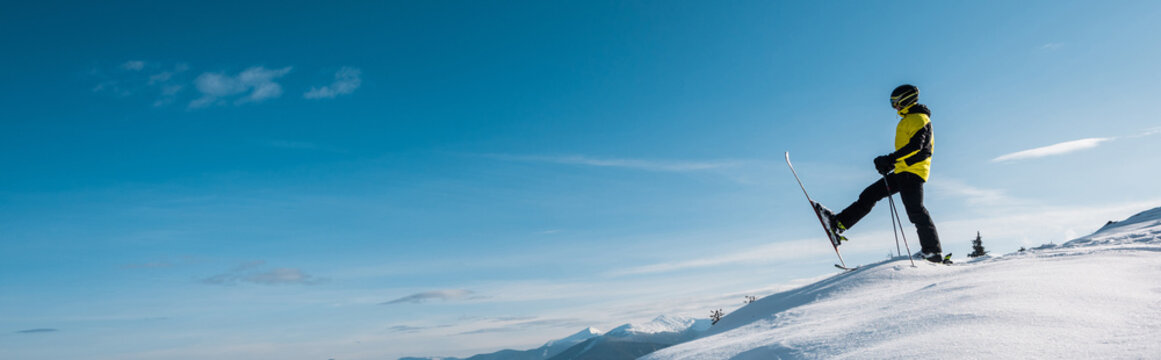 panoramic shot of skier holding ski sticks and making step against blue sky in mountains