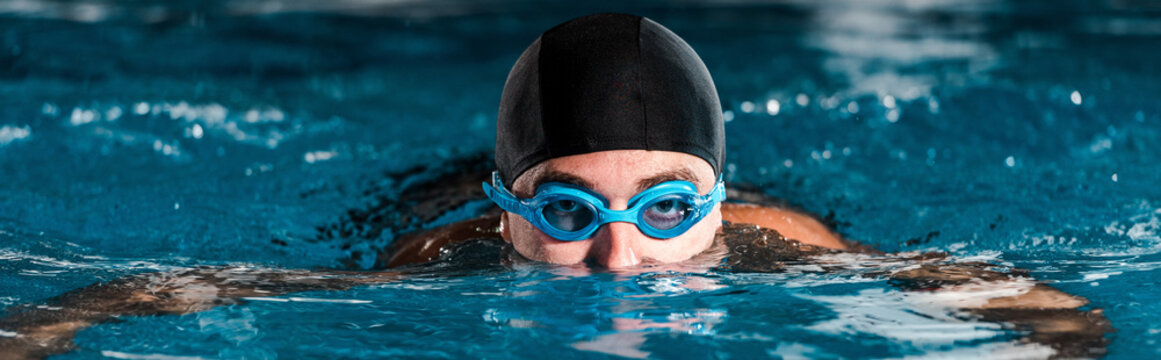 panoramic shot of athletic man in goggles training in swimming pool