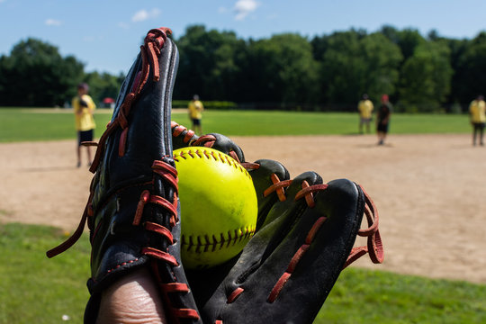 a man holds a freshly caught green softball in a black baseball glove during a softball tournament game with teammates in the background