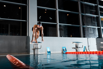 handsome and shirtless swimmer standing in starting pose on diving block Wall mural