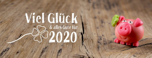 Foto auf AluDibond Individuell New year card 2020, german language - Good luck and best wishes for 2020 - Marzipan pig on rustic wooden background - Good luck symbol