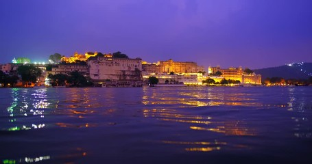 Wall Mural - Udaipur City Palace on bank of Pichola lake with water ripples - Rajput architecture of Mewar dynasty rulers of Rajasthan. Sunset at Udaipur, India
